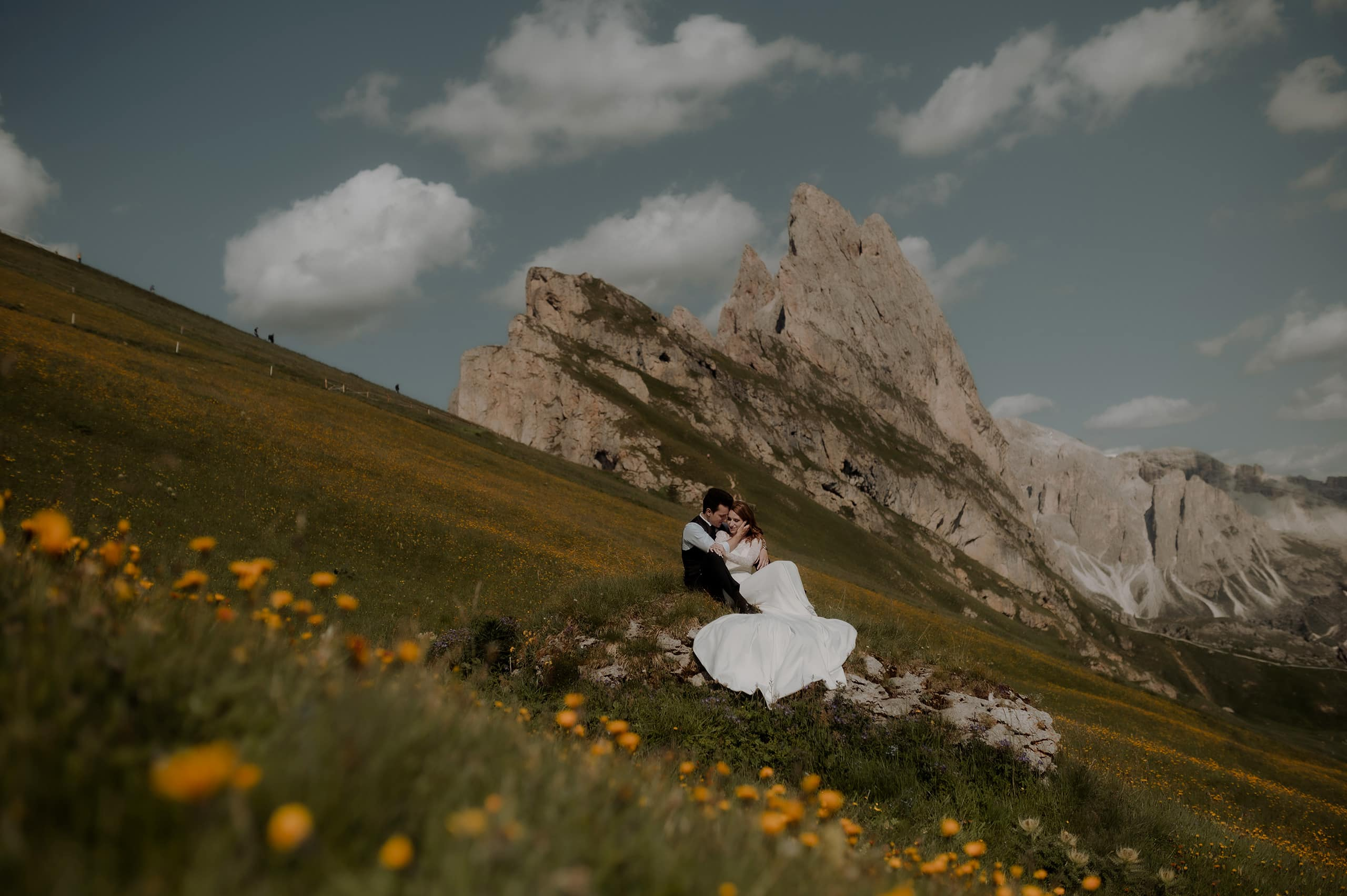 Bride and groom on a rock with flowers at Seceda in the Italian Dolomites with their Italy Elopement Photographer