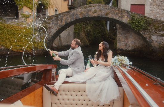Lake Como Elopement - Bride and groom popping champagne from the boat at Lake Como in Italy