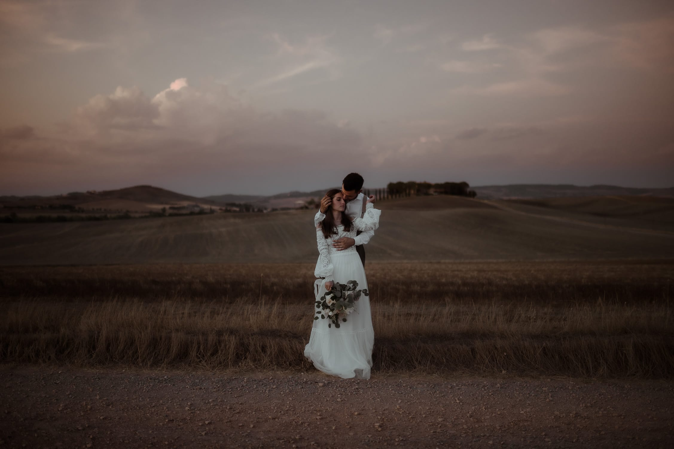 Tuscany Elopement Wedding | Bride and groom in a field at sunset at Pienza in Val d'Orcia