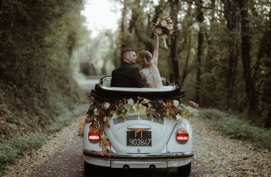 Bride and groom on a vintage VW white car with flowers while kissing in a forest in Italy | Elopement Definition