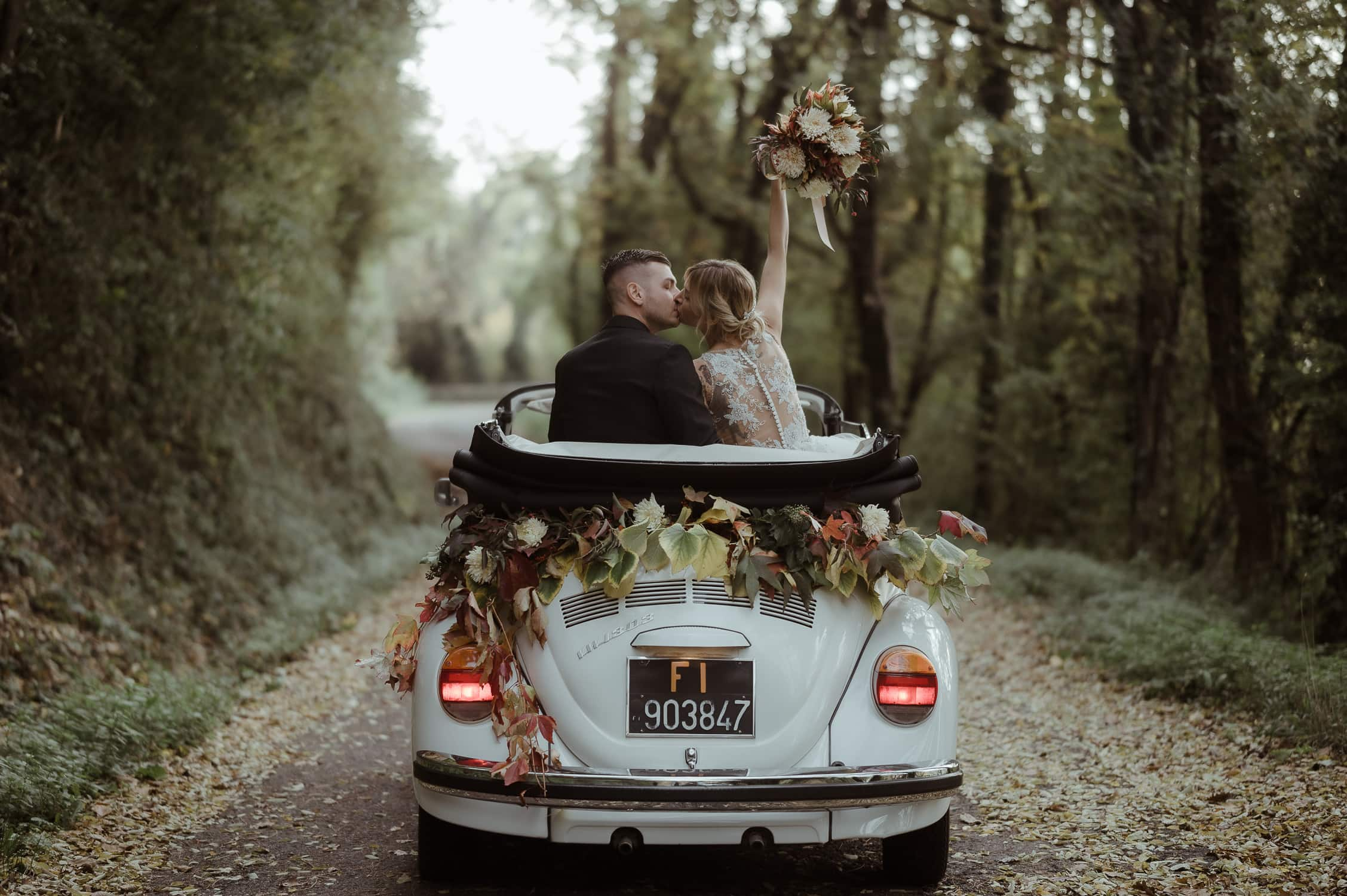 Bride and groom on a vintage VW white car with flowers while kissing in a forest in Italy   Elopement Definition